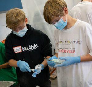 Two participants of the Advanced 3D Printing & Manufacturing Summer Camp hosted by Additive Manufacturing Institute of Science & Technology (AMIST) are shown brushing off excess material from their 3D printed projects.
